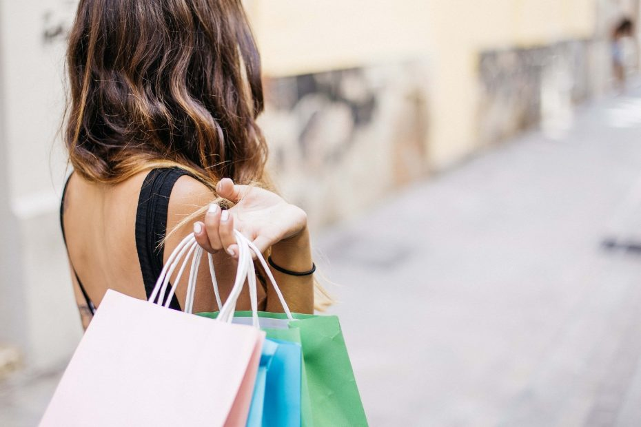Woman carrying many shopping bags needs help to stop overspending
